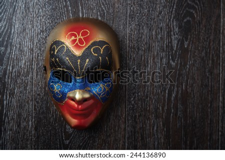 Carnival Venetian mask on a hardwood wall. Horizontal photo - stock photo