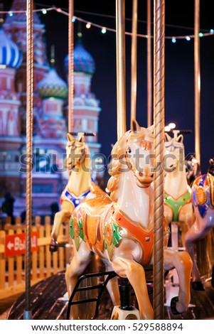 Carousel horses at the Christmas Fair on the background of St. Basil's Cathedral. Red Square. Night. Moscow, Russia
