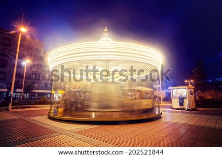 carousel with motion lines at night - stock photo