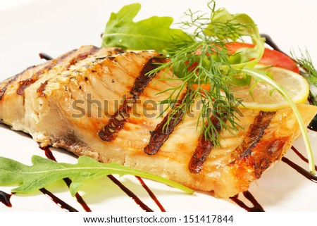 carp fillet decorated with leaves of arugula, lemon and dill - stock photo