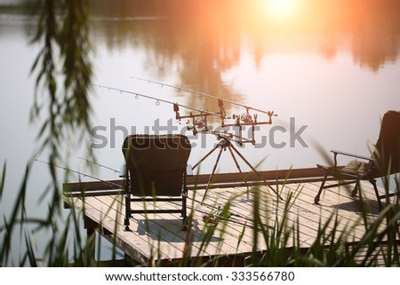 Carp spinning reel angling rods on pod standing between two black comfortable armchairs on wooden pier with beautiful picturesque view summer vacation tranquility, horizontal picture - stock photo