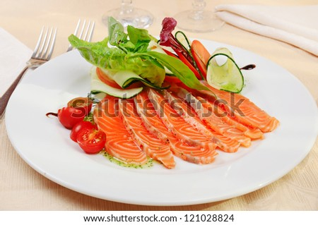 Carpaccio of salmon with cherry tomatoes in restaurant - stock photo
