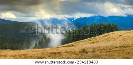 Carpathian autumn mountains with beautiful colorful clouds. Forest in a fog