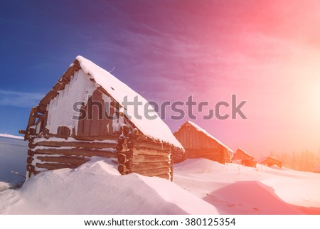 Carpathian mountain village with old rustic houses covered by fresh snow in a beautiful sunlight. Sunny winter day. Ukraine, Europe - stock photo