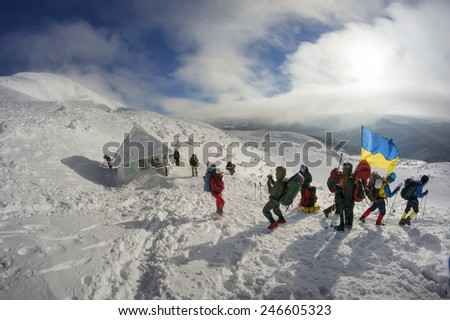 Carpathian Mountains, Ukraine-January 8, 2015: Climbing the Christmas Ukrainian climbers on the top of the main country with the state  the flag and the Rebel Army Roman Shukhevych and Stepan Bandera