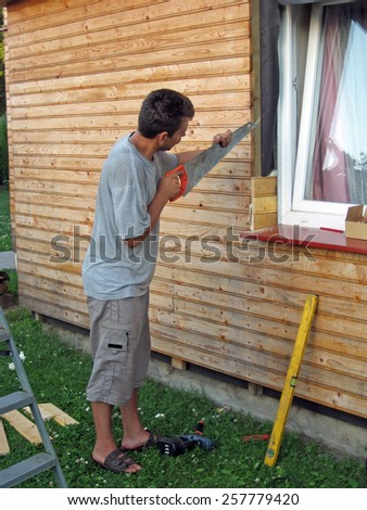Carpenter at work making wall from wooden boards - stock photo