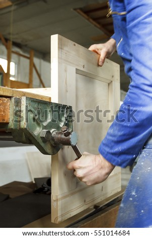Carpenter at work using a vice in his workshop.