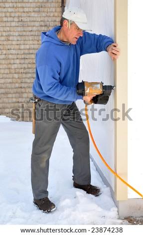 Carpenter attaches corner board to addition with nail gun - stock photo
