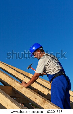 Carpenter building roof structure - driving in large nail - stock photo