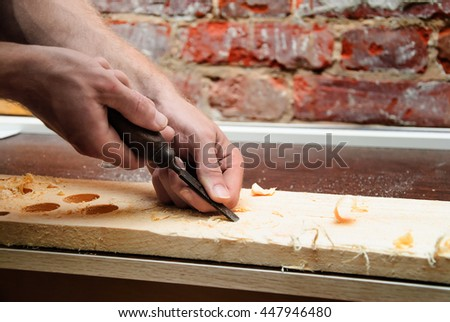 Carpenter carving wood with a chisel in a carpentry