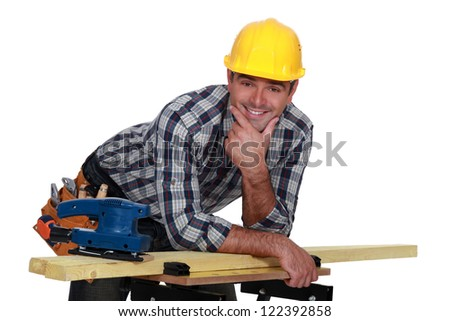 Carpenter casually leaning on work bench - stock photo