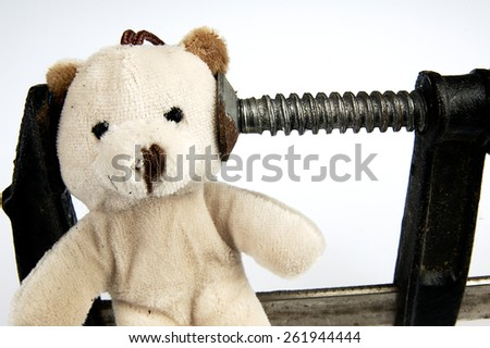 Carpenter clamp on the head teddy bear. The idea for the show stress and overload. - stock photo