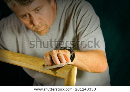 Carpenter contractor man skillfully sanding and preparing wooden molding for door framing on home interior repair project - stock photo