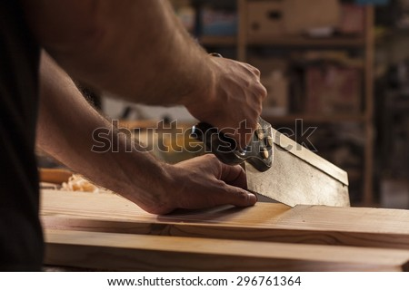 carpenter cutting planks with wood saw - stock photo