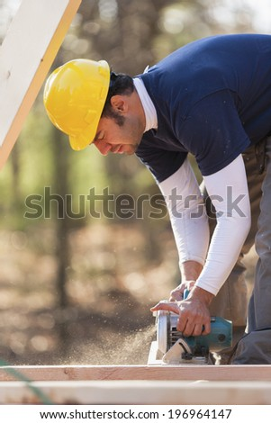 Carpenter cutting rafters and joists with circular saw