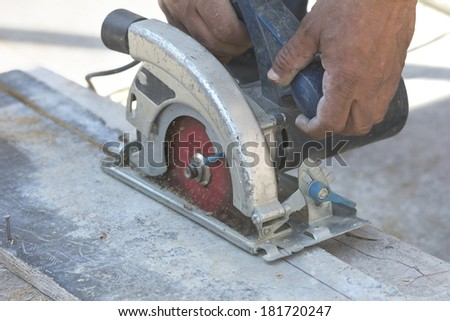 Carpenter cutting wood with electric saw on construction site