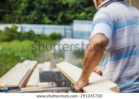 Carpenter cutting wood with electric saw outdoor - stock photo