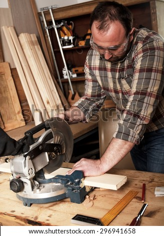 Carpenter cutting wooden plank with circular saw in his workshop.