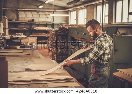 Carpenter doing his job in carpentry workshop. - stock photo