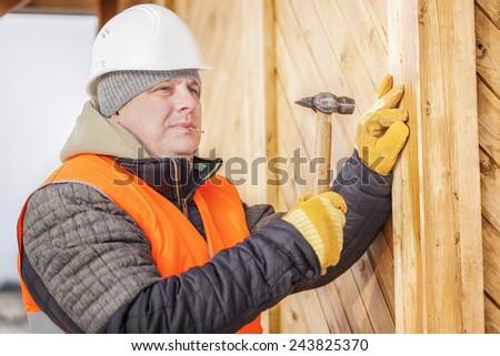 Carpenter drives a nail in board - stock photo
