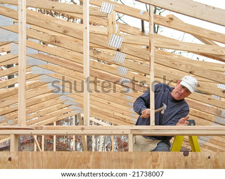 Carpenter framing gable end, with many roof trusses in background - stock photo