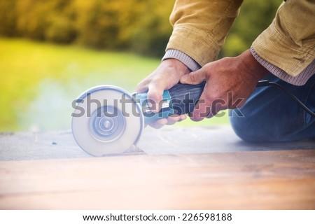 Carpenter grinding wooden planks  - stock photo