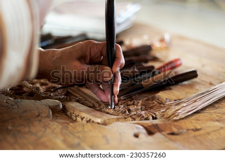carpenter hand carving wood with care - stock photo