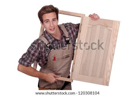 Carpenter holding cupboard door - stock photo