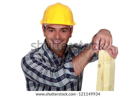 Carpenter holding planks of wood - stock photo