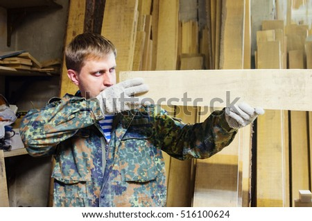 Carpenter inspects the wood