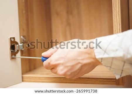carpenter installing  furniture door hinge and using screwdriver. - stock photo