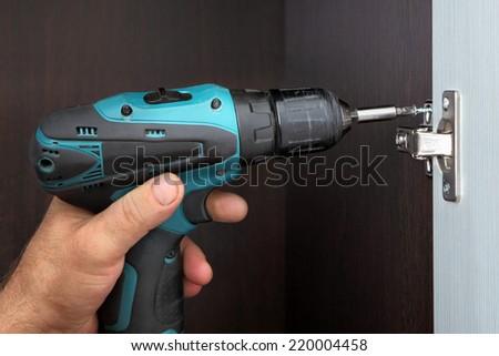 Carpenter installs door wardrobes, screw the door hinge cordless screwdriver. - stock photo