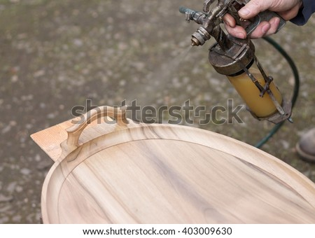 Carpenter is covering stool by lacquer. Furniture varnishing using sprayer (pulverizer). - stock photo