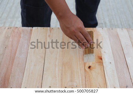 Carpenter is painting a wood with lacquer