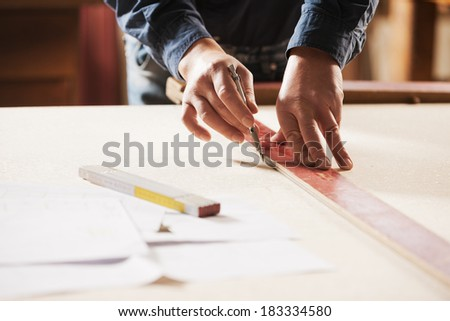Carpenter measuring and tracing lines with a ruler on a wooden surface.