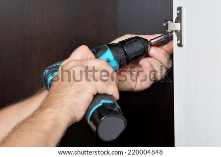 Carpenter mounts wardrobe, screwing a screw, furniture door hinge, using cordless screwdriver. - stock photo
