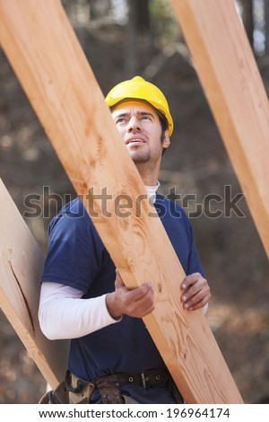 Carpenter placing roof rafters in place on a new home construction site - stock photo