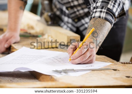 Carpenter plans project and writes at drawings in workshop - stock photo