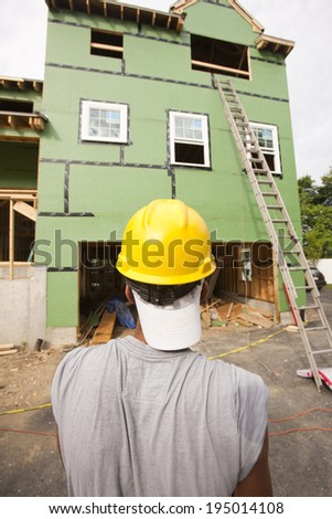 Carpenter reviewing window installation for second story of a new home - stock photo
