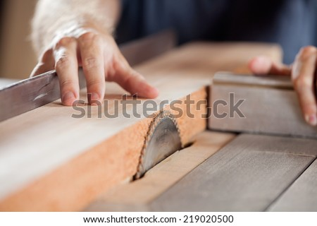 Carpenter's hands cutting wood with tablesaw in workshop - stock photo