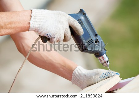 Carpenter's hands man worker drilling wood at construction site - stock photo