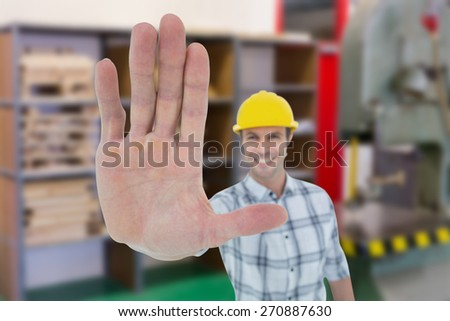 Carpenter showing palm over white background against workshop - stock photo
