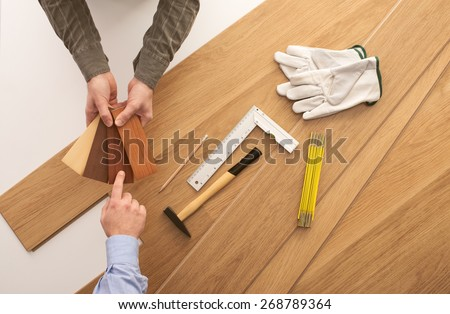 Carpenter showing some wooden baseboard swatches to a customer and choosing a color, flooring installation and work tools on background - stock photo