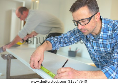 Carpenter sing a tape measure - stock photo