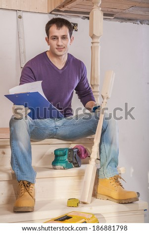 carpenter sitting on steps of wooden ladder holding clipboard with white sheet and wooden post