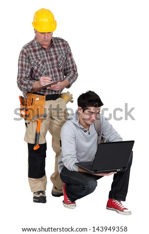 Carpenter stood by young apprentice using laptop - stock photo