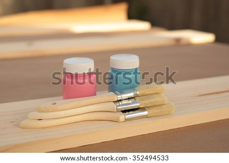 carpenter table with pine wood, paint blue, pink and several brushes