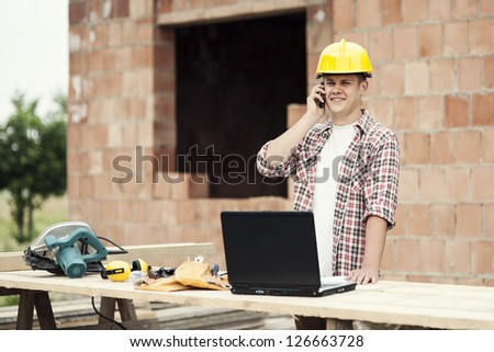 Carpenter talking on mobile phone - stock photo