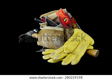Carpenter tools, hammer, nails, screws, level, tape measure, screwdrivers, pliers, gloves, toolbag and hacksaw isolated on black background - stock photo