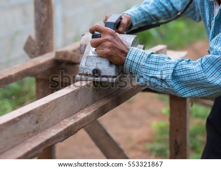 carpenter using electric planer with wooden plank in carpentry workshop